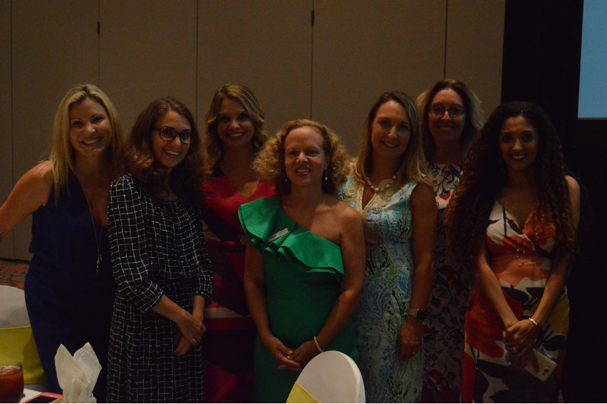 Left to right: Justine Florez, Erin Frye, Jamie Stoll, Laura Reece, Erin Fulton, Jean Dwyer and Nada Manley pose for a photo at Power of the Purse on Friday. Photo by Tim Briggs