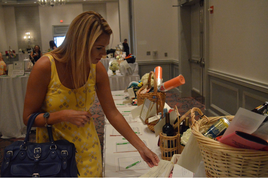 Jamie Brown looks at items at Power of the Purse silent auction on Friday. Photo by Tim Briggs