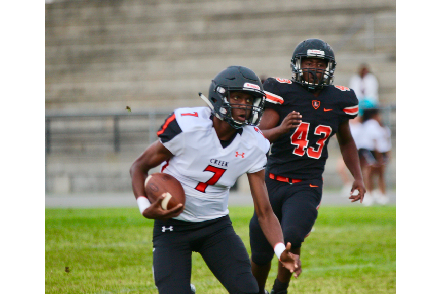Junior quarterback Jason McCoy runs with the ball against Leesburg. Photo by Ray Boone
