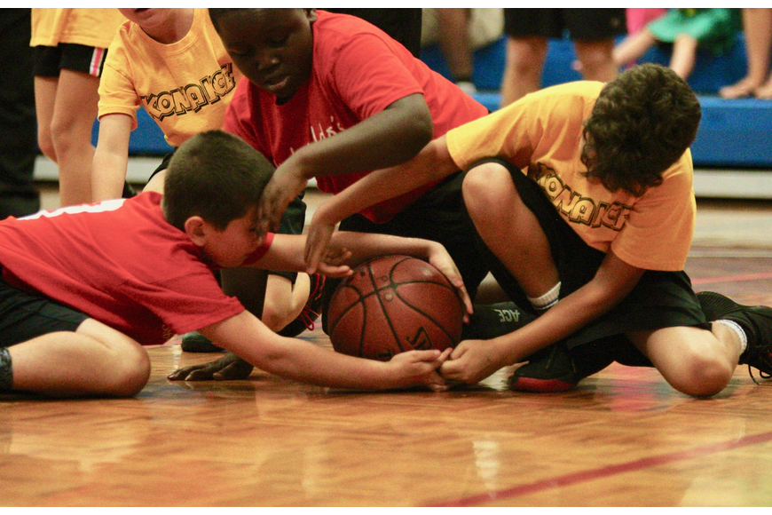 Opposing players fight for the ball during a PAL game. Photo by Ray Boone