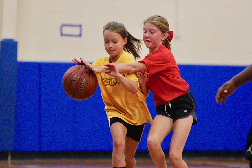 Jovie Graham (yellow) dribbles the ball up the court during a PAL game. Photo by Ray Boone