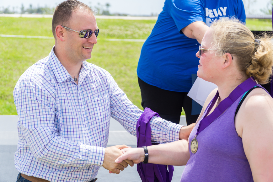 Julie Schlack receives a survivor metal from Councilman Chase Tramont at the Relay for Life at Riverwalk Park in Port Orange. Photo by Zach Fedewa