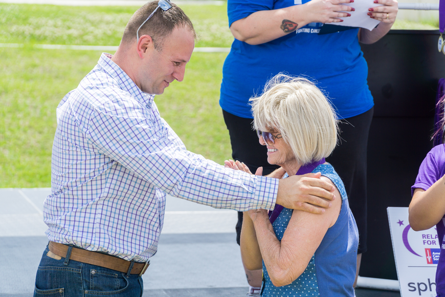 Kathy Z receives a survivor metal from City Councilman Chase Tramont at the Relay for Life at Riverwalk Park in Port Orange. Photo by Zach Fedewa
