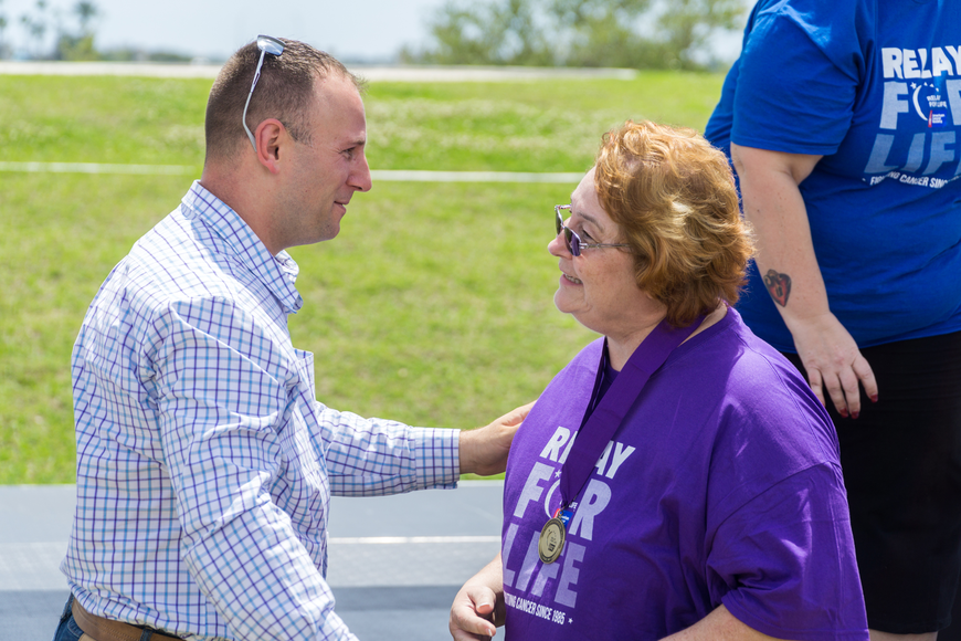 Anne Banderford receives a survivor metal from Councilman Chase Tramont at the Relay for Life at Riverwalk Park in Port Orange. Photo by Zach Fedewa