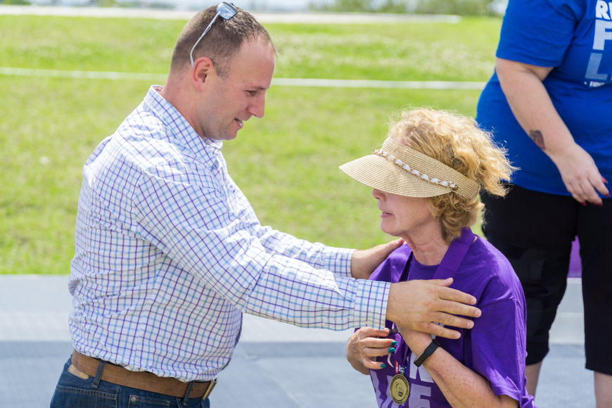 Bonita Adamson receives a survivor metal from Councilman Chase Tramont at the Relay for Life at Riverwalk Park in Port Orange. Photo by Zach Fedewa