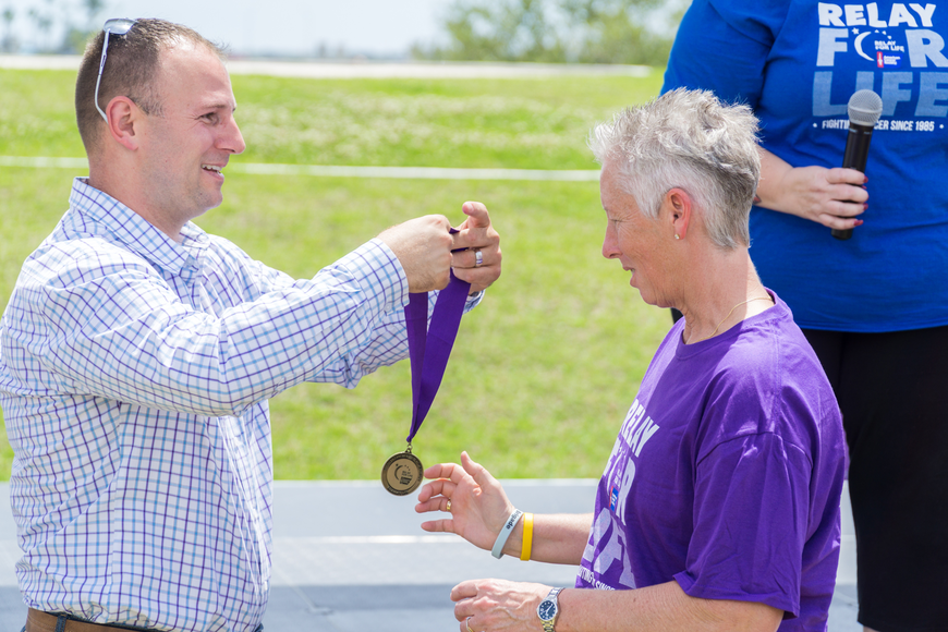 Shelly Lewis receives a survivor metal from Councilman Chase Tramont at the Relay for Life at Riverwalk Park in Port Orange. Photo by Zach Fedewa