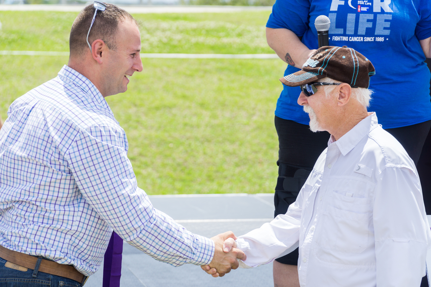 Phil Hanerhan receives a survivor metal from Councilman Chase Tramont at the Relay for Life at Riverwalk Park in Port Orange. Photo by Zach Fedewa