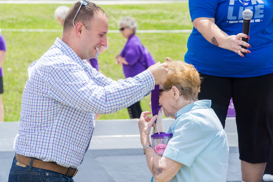 Lolli Fricki receives a survivor metal from Councilman Chase Tramont at the Relay for Life at Riverwalk Park in Port Orange. Photo by Zach Fedewa