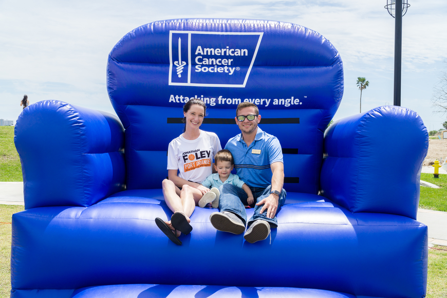 Rebecca, Noah and City Council candidate Jonathan Foley sit on the American Cancer Society blow up chair at the Relay for Live at Riverwalk Park in Port Orange. Photo by Zach Fedewa